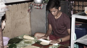A local man flatten a dough for the Empanada.
